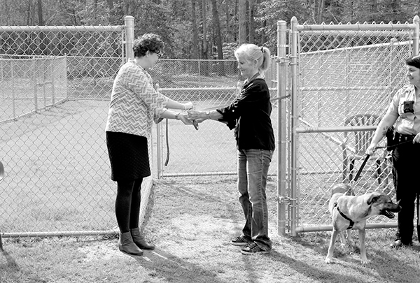 GMHS Executive Director April Martinez and Gloucester Animal Shelter volunteer Joyce Emerson cut the ribbon on the shelter's new dog runs. At right, Medina the dog, held by Gloucester deputy animal control officer Jacky Wilson, waits her turn to try out the facility. Photo by Melany Slaughter