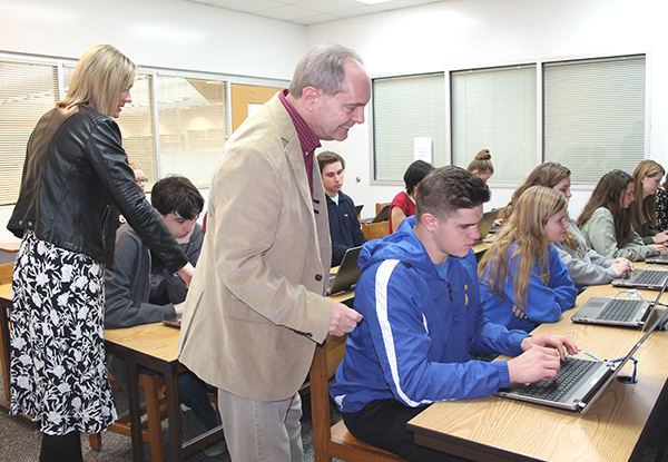Mathews County Electoral Board Secretary Jeff Bohn, center, assists Mathews High School senior Josh Monastyrly as he registers to vote. Bohn, Electoral Board President Josie Thorpe (not pictured), and Mathews Voter Registrar Carla Faulkner, at left, worked with seniors over a two-day period to encourage them to participate in elections. The students shown here are in teacher Al Thomas's Honors U.S. Government class. Photo by Sherry Hamilton